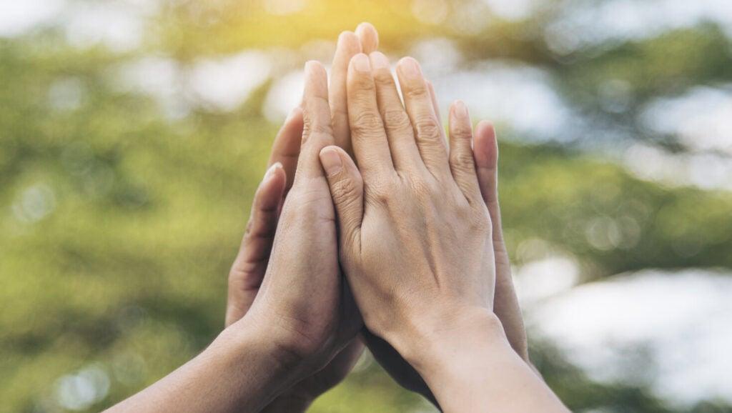 Hands high-fiving outdoors