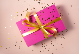 A pink gift box with gold ribbon and glitter scattered over it